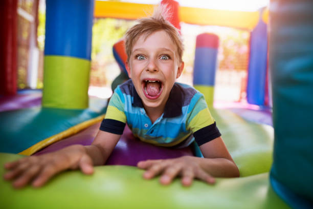 Little boy having fun in inflatable castle playground stock photo