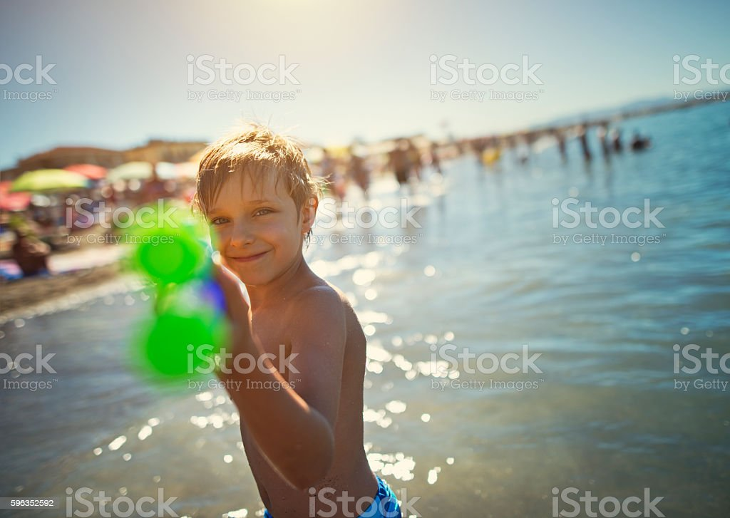 Little boy having fun in sea with watergun royalty-free stock photo