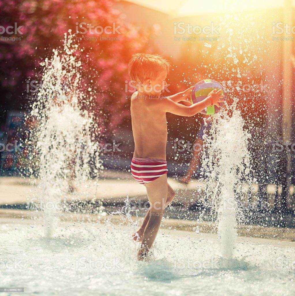 Little boy having fun in water park fountain pool stock photo