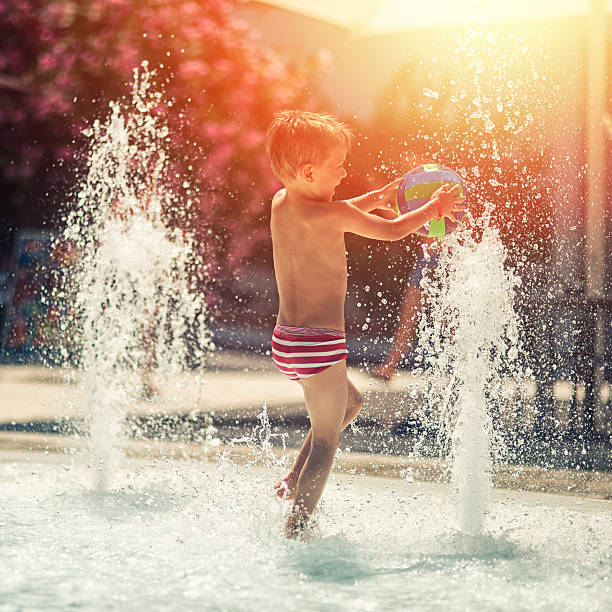 Little boy having fun in water park fountain pool stock photo