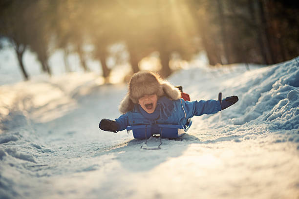 Little boy having fun on his sled in winter worest. stock photo
