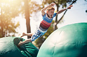 Little boy having fun in inflatable bouncy castle playground. Sunny summer day\nNikon D810