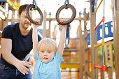 Little boy having fun on outdoor playground. Summer active sport leisure for kids. Kindergarten or school yard. Toddler child activity