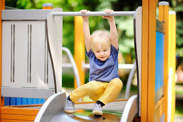 Little boy having fun on outdoor playground/on slide stock photo