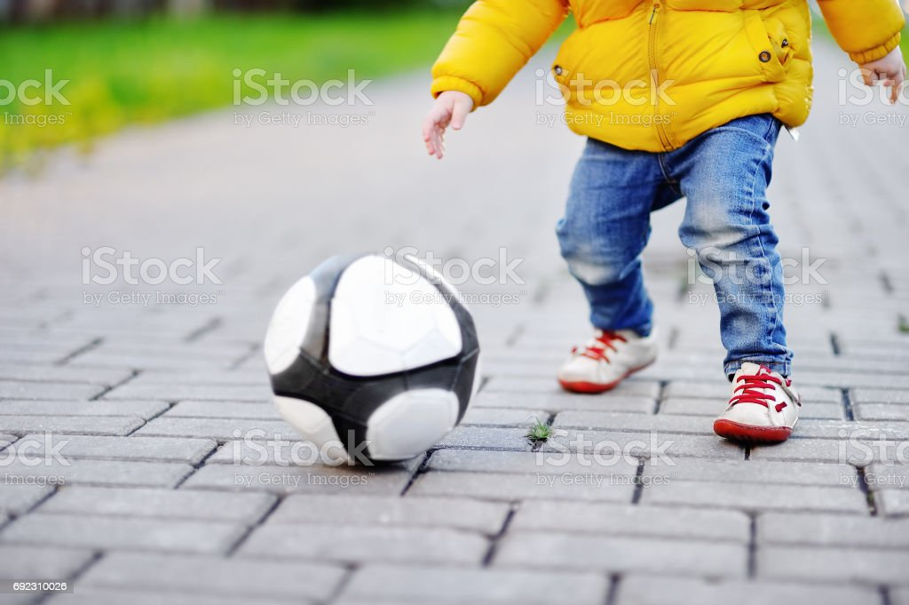 Little boy having fun playing a soccer game on sunny spring or autumn day stock photo