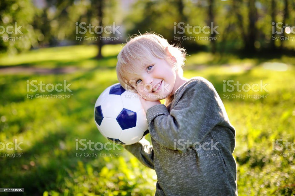Little boy having fun playing a soccer game on sunny summer day stock photo