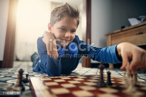 Little boys aged 9 is playing chess on the floor. Nikon D850
