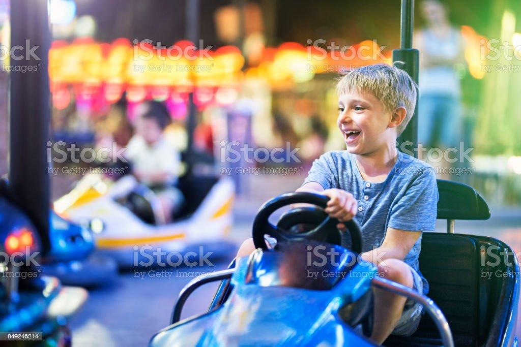 Niño que se divierte el coche de parachoques del montar a caballo - foto de stock