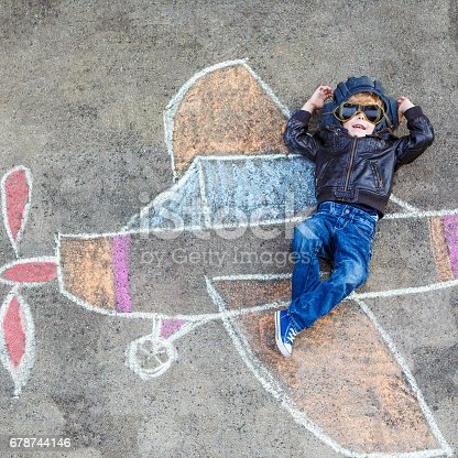 istock Little boy having fun with airplane picture drawing with chalk 678744146
