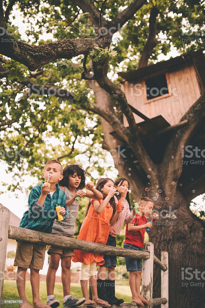 Little boy having fun with friends in park blowing bubbles stock photo