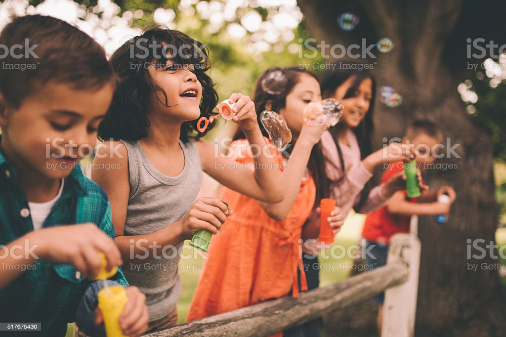 Little boy having fun with friends in park blowing bubbles royalty-free stock photo