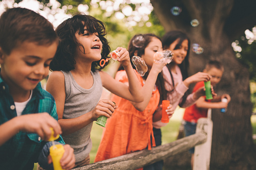 Long haired hispanic boy laughing and having fun with his friends standing on a wooden fence in a summer park blowing bubbles, with a vintage develop
