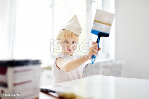 657926276 istock photo Little boy having fun with paint brush during repair of room 1195374750