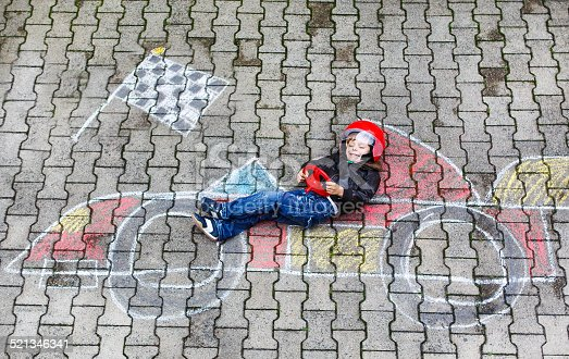 istock Little boy having fun with race car chalk picture 521346341