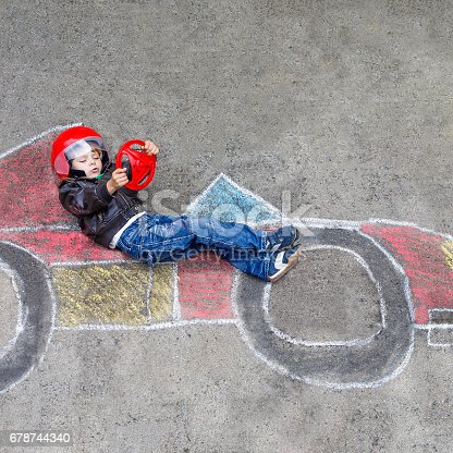 istock Little boy having fun with race car drawing with chalks 678744340