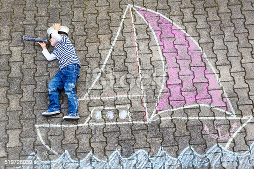 istock Little boy having fun with ship picture drawing with chalk 519728039