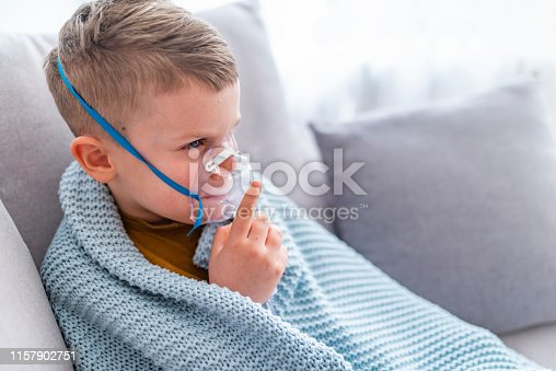 Caucasian child holding oxygen or inhaler mask at home. Small boy does therapeutic inhalation using a nebulizer. Child with asthma problems making inhalation with mask on his face