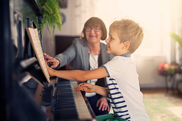 Little boy having piano lesson stock photo