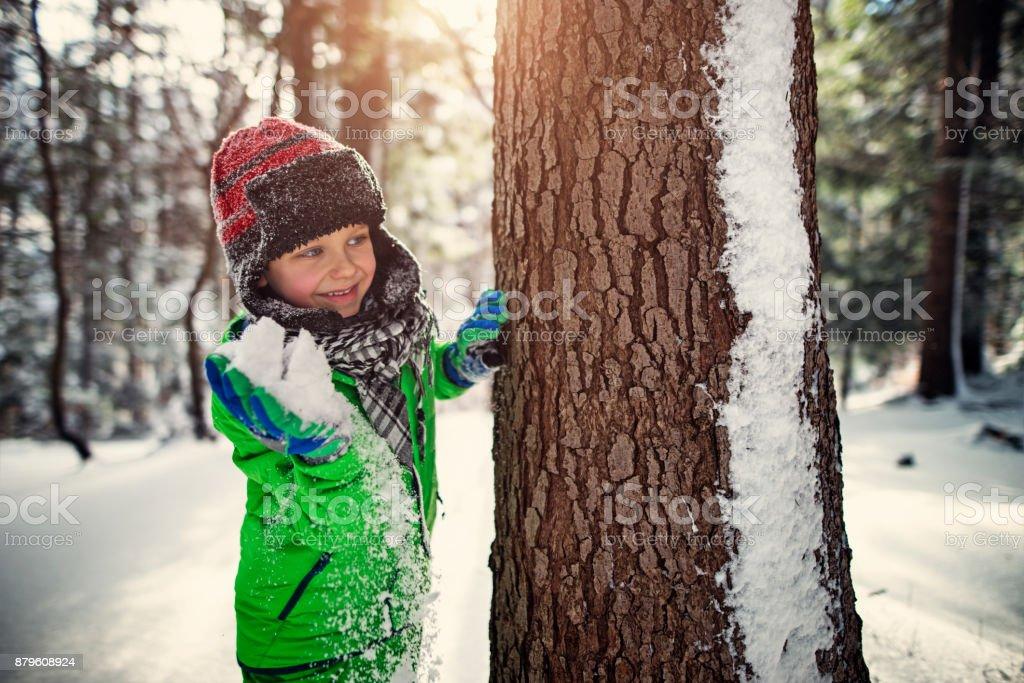 Petit garçon ayant showball combattre dans la forêt d'hiver - Photo