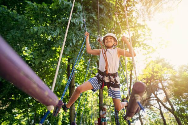 Kleiner Junge haben Schwierigkeiten mit dem Gleichgewicht im Hochseilgarten – Foto