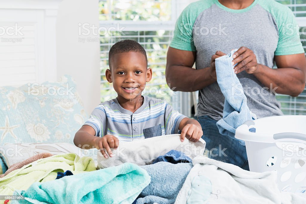 Little boy helping his father fold laundry stock photo