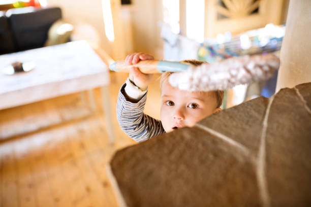 Little boy helping with house chores, dusting stock photo