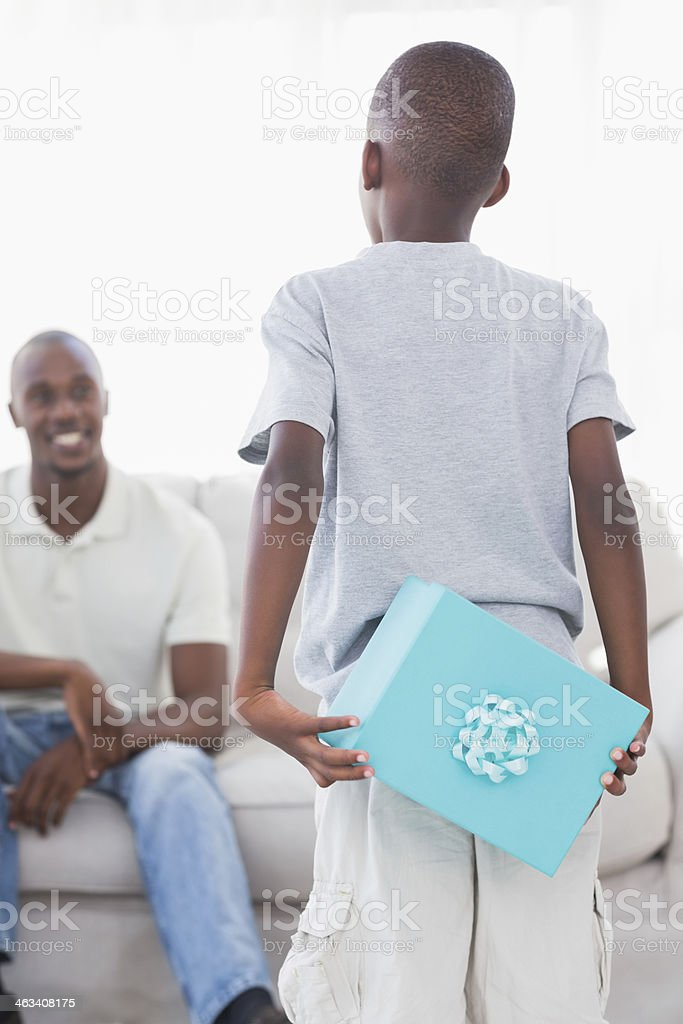 Little boy hiding present for smiling father behind his back stock photo