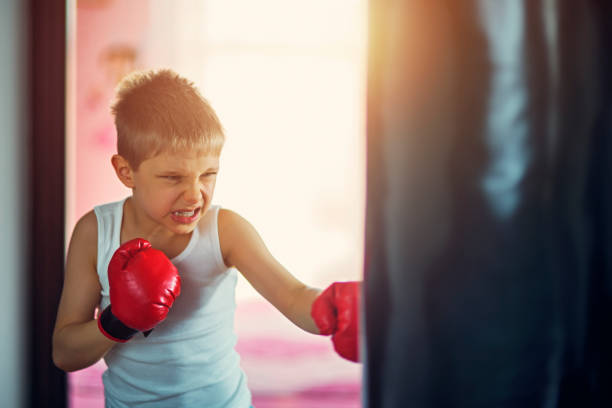 Little boy hitting hard punching bag stock photo