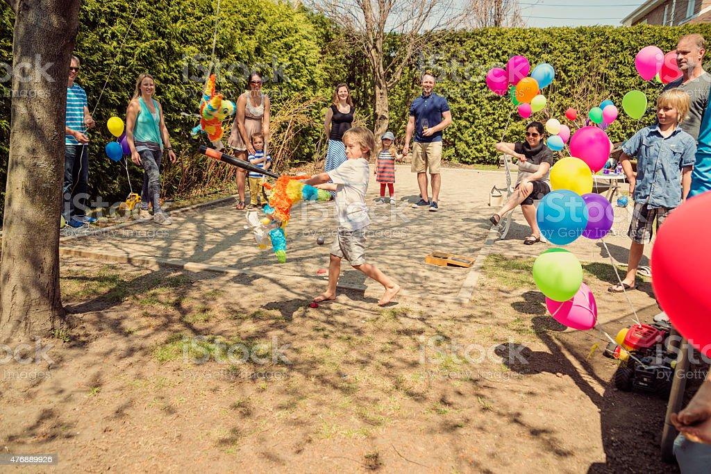 Маленький мальчик, жесткой pinata на день рождения в пригород заднем дворе. стоковое фото