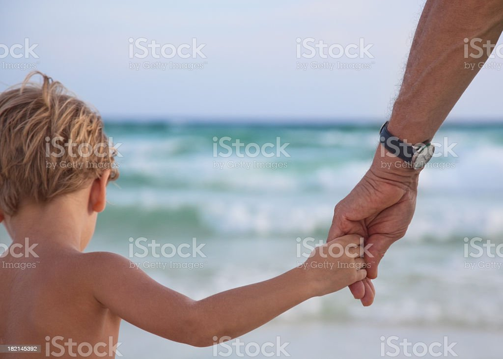 Little boy holding a man's hand at the beach royalty-free stock photo