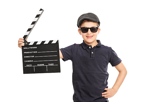 kleiner junge hält ein film clapperboard - klappe hut stock-fotos und bilder