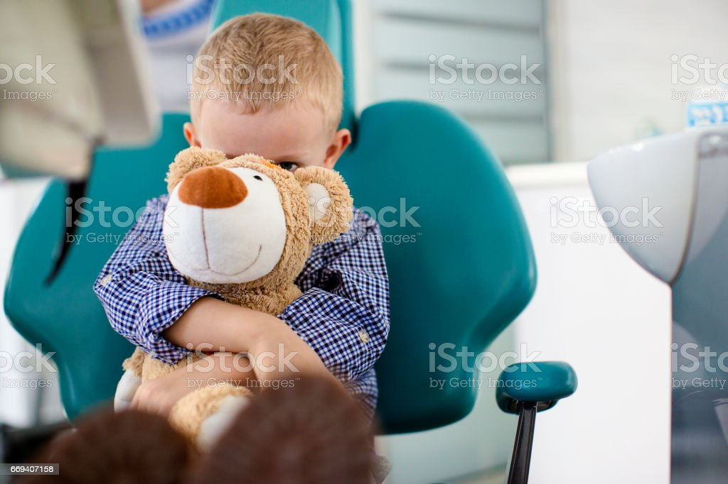 Little boy holding a teddy bear in his arms at dentists office stock photo