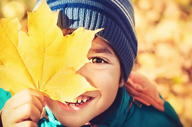 Kleiner Junge hält eine gelbe Ahorn Blätter – Foto