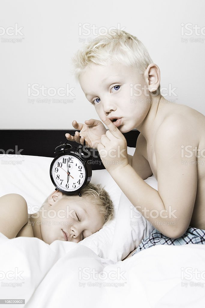 Little Boy Holding Alarm Clock to Sleeping Brother stock photo