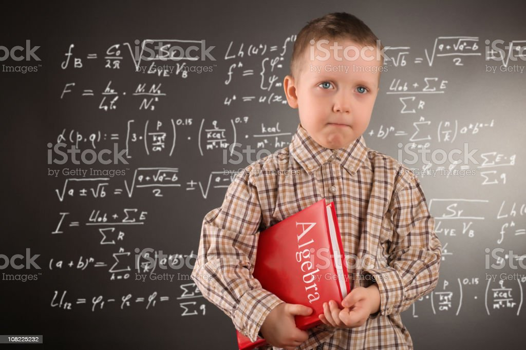 Little Boy Holding Algebra Book Against Blackboard of Calculations royalty-free stock photo