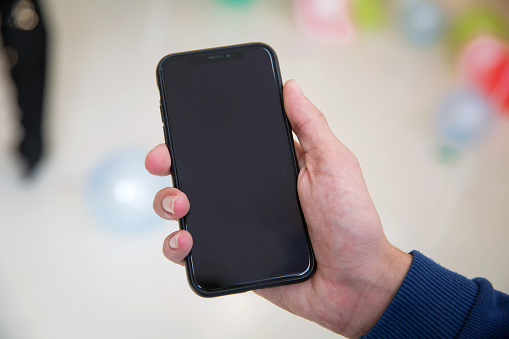 istock Little boy holding black modern smartphone with empty screen in hand, isolated on blurred background . Mockup 1218581894