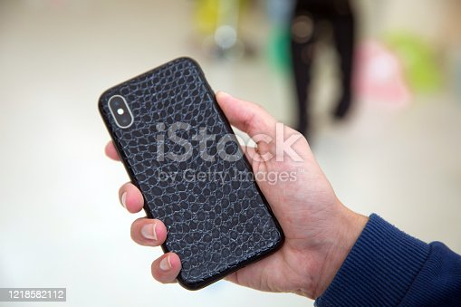 istock Little boy holding black modern smartphone with empty screen in hand, isolated on blurred background . Mockup 1218582112