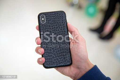 istock Little boy holding black modern smartphone with empty screen in hand, isolated on blurred background . Mockup 1218582131