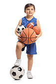 Full length portrait of a little boy holding different kinds of sports balls isolated on white background