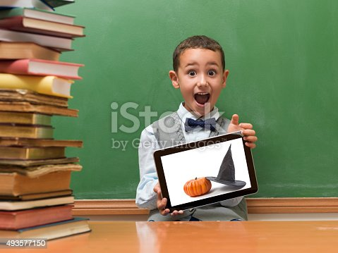 istock Little Boy Holding Digital Tablet Displaying Halloween Photo 493577150