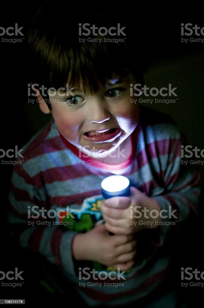Little Boy Holding Flashlight Up to Face, Low Key stock photo