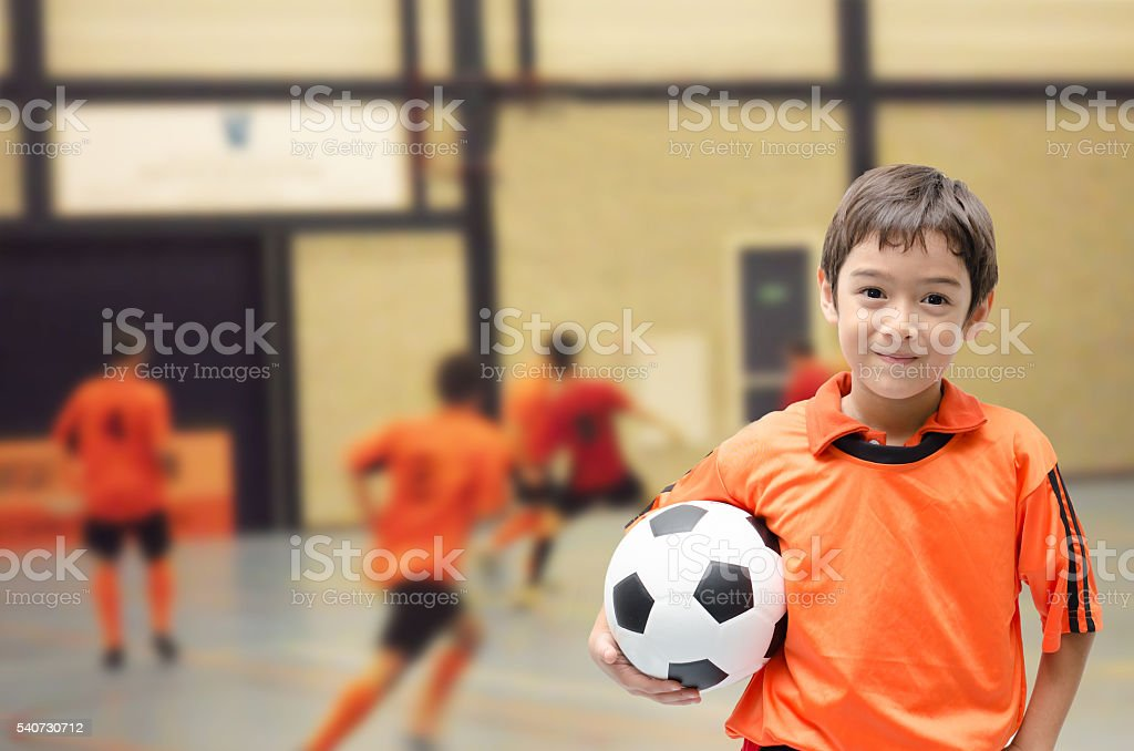 Little boy holding football in futsal gym stock photo