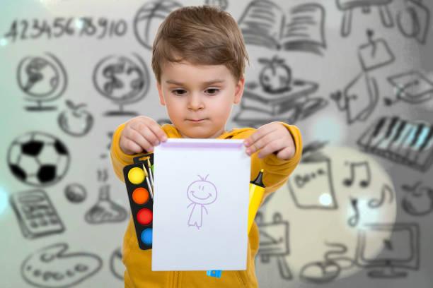 little boy holding his first drawing - sprüche kinderlachen stock-fotos und bilder