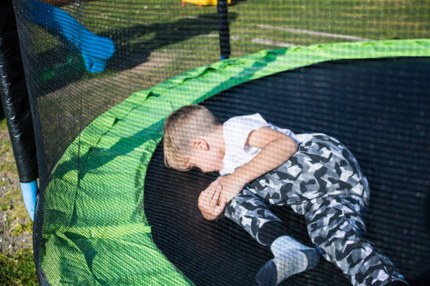 Little boy holding his knee in pain while jumping on trampoline.