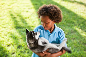 Little boy (7 years) holding husky puppy.