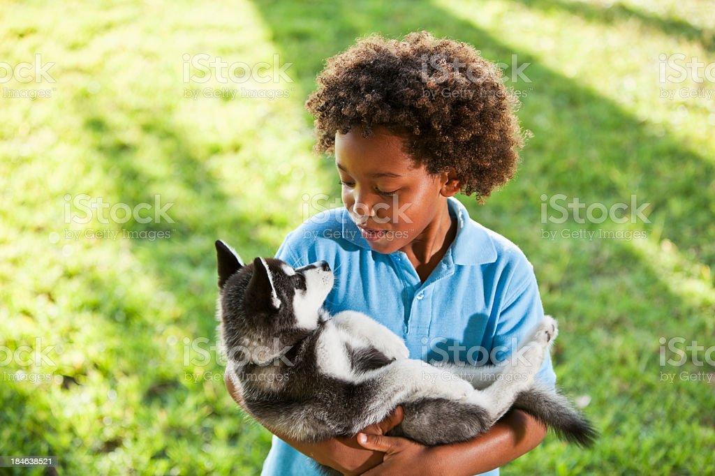 Little boy holding husky puppy stock photo