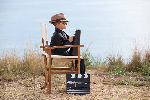 kleiner junge hält megafon und sitzt auf regiestuhl - klappe hut stock-fotos und bilder