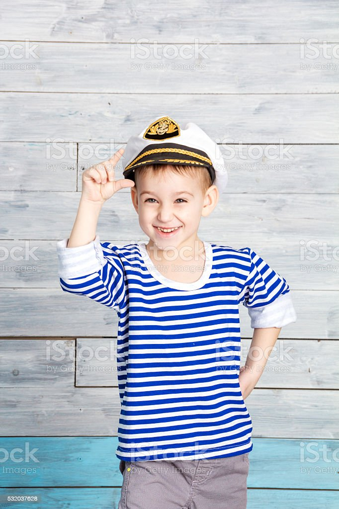 little boy holding on to his cap and laughs stock photo