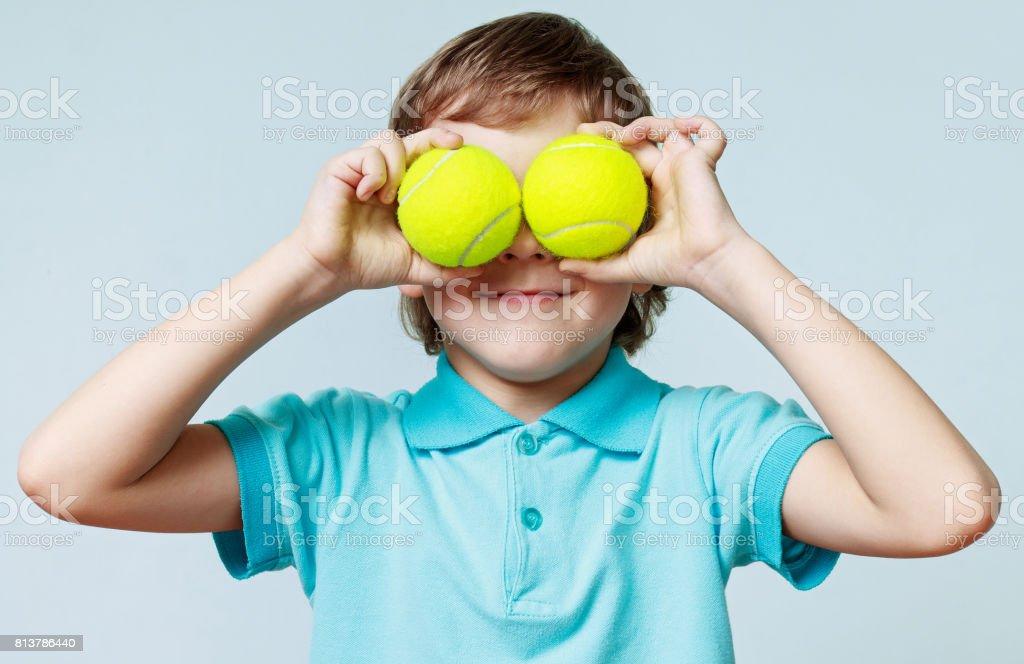 Petit garçon tenant des balles de tennis au lieu des yeux, souriant - Photo