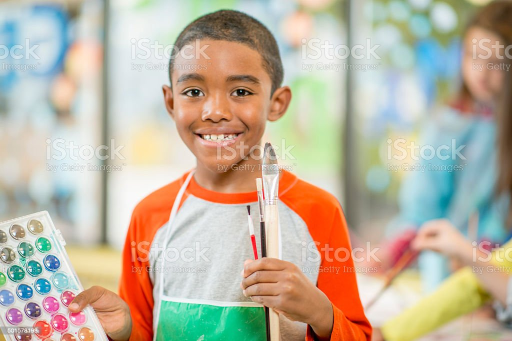Little Boy Holding Up His Paint Colors stock photo